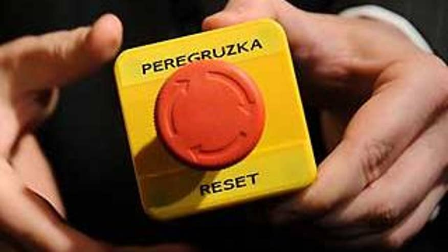 An assistant shows the mock 'reset' button that Secretary of State Hillary Clinton handed to Russian Foreign Minister Sergei Lavrov in Geneva Friday. (AP Photo)