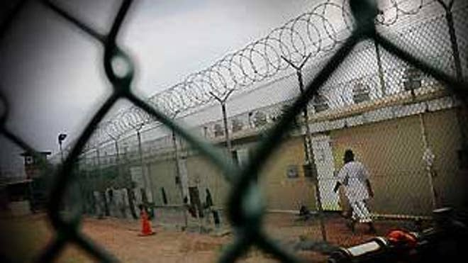 A detainee walks in Camp 4 at the Guantanamo Bay detention facility. (AP Graphic)