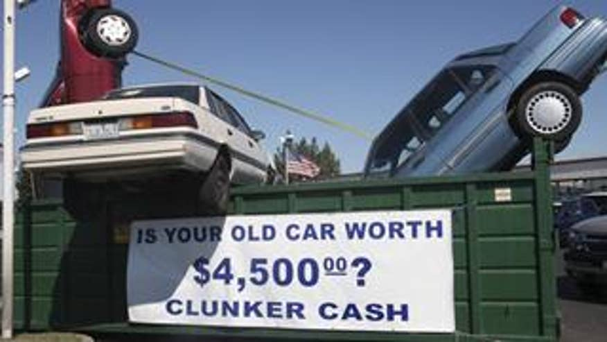 "Used cars are seen in a dumpster to draw attention to the ""Cash for Clunkers"" program"