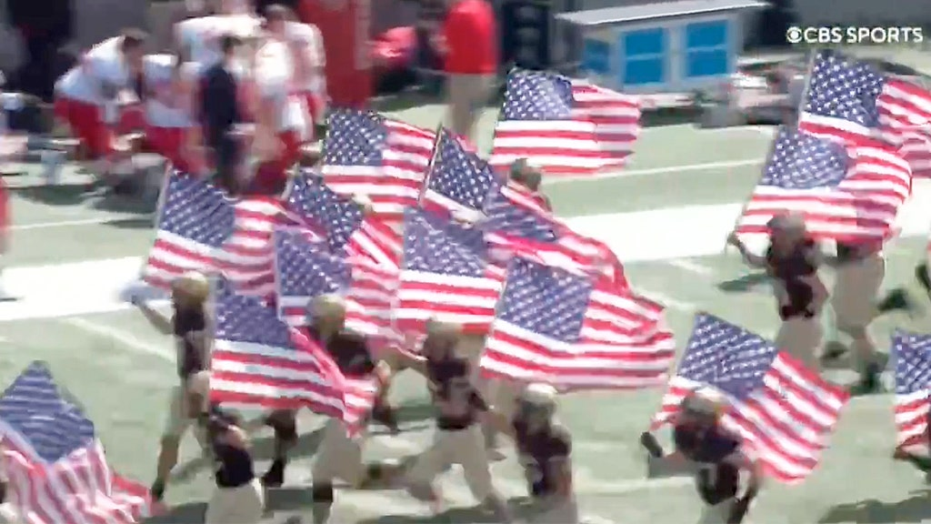 Players run out  with American flags in support of victims of the 9/11 attacks