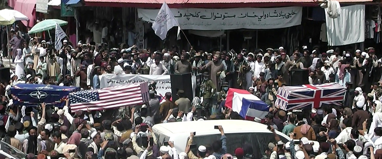 Taliban supporters in Afghanistan drape flags over coffins, hold mock funeral for America, west