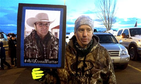 FILE - This Jan. 30, 2016 file photo shows Tony Atencio of Burns, Oregon, holds a photo of rancher Robert ``LaVoy'' Finicum at a rally against in Burns, Ore.  The funeral for Finicum, killed by law enforcement during the armed occupation of an Oregon wildlife refuge was expected to draw supporters Friday, Feb. 5, from around the West to a small Utah town. (AP Photo/Nicholas K. Geranios, File)