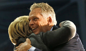 FILE This Monday Feb. 29, 2016 file photo shows Virginia Gov. Terry McAuliffe, right, as he hugs Democratic presidential candidate Hillary Clinton as she arrives to speak at a campaign rally in Norfolk, Va. Virginia was supposed to be a key battleground state and the high energy governor was expected to spend the weeks leading up to Election Day bouncing around the Old Dominion to help longtime pal Hillary Clinton win the state's 13 electoral votes. (AP Photo/Gerald Herbert)