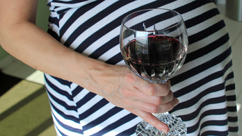 Pregnant woman with a glass of red wine highlighting the arguments against drinking whilst pregnant