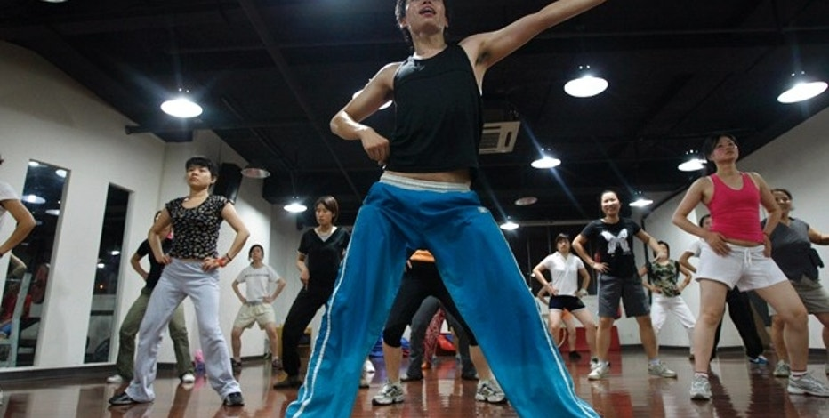 People exercise in an aerobics class at Kangmei gym in the residential area of Hongkou district in Shanghai July 9, 2007. As the booming development of domestic economics, gym exercise has becomes one of the most popular civil sports in China nowadays.  REUTERS/Nir Elias (CHINA)