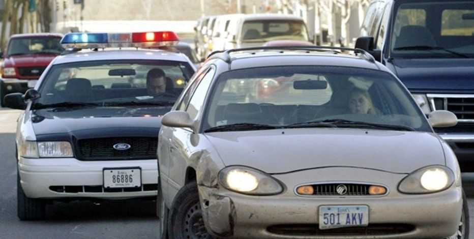FILE: A motorist whose car has its two front wheels opposing each other is pulled over by a policeman for a moving traffic violation.