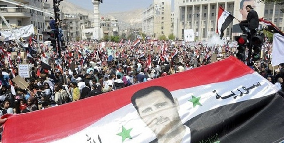 March 29: Syrians display a giant national flag with a picture of Syria's President Bashar al-Assad during a pro-government rally at the central bank square in Damascus.