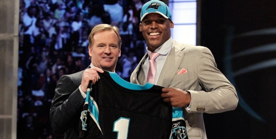 Quarterback Cam Newton of Auburn University stands with NFL Commissioner Roger Goodell after being selected as the first overall pick by the Carolina Panthers in the 2011 NFL football Draft in New York, April 28, 2011.