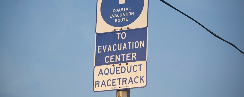 """The """"Coastal Evacuation Route"""" sign is seen in Rockaway, New York, August 26, 2011. New York City on Friday ordered the evacuation of more than 250,000 people and prepared to shut down its entire mass transit system, both unprecedented measures ahead of the expected battering from Hurricane Irene. The powerful and unusually large storm trudged up the U.S. East Coast on Friday, threatening 55 million people including more than 8 million in New York City, which was expecting heavy winds late on Saturday or early on Sunday. REUTERS/Allison Joyce (UNITED STATES - Tags: ENVIRONMENT DISASTER)"""