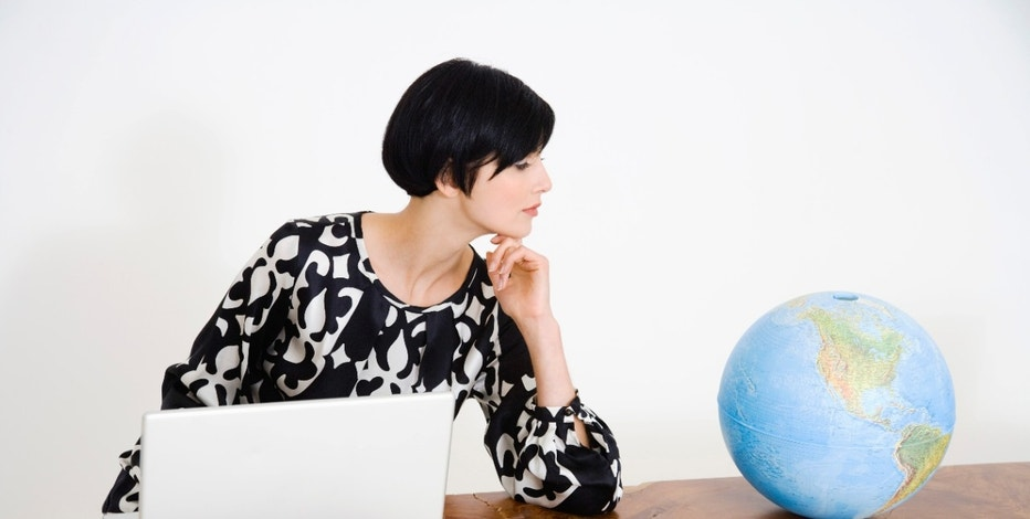 Woman with a globe and laptop computer