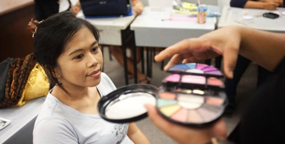 An instructor applies make-up on a participant during a make-up workshop for Indonesian domestic workers during their day off at the Sekolah Indonesia Singapura (Indonesian School) in Singapore December 12, 2010. Administered by the Indonesian Embassy, the school offers courses from high school diplomas to degree programs held in partnership with the Indonesian Open University for Indonesia migrant domestic workers on Sundays, the sole off day for the majority of such workers. More than 150 domestic workers are currently enrolled in open degree courses, while about 500 others also take part in a variety of enrichment courses ranging from sewing, computer classes and English. There are currently about 85,000 Indonesian domestic workers in Singapore, according to local media. December 18 marks the International Migrants Day. REUTERS/Edgar Su (SINGAPORE - Tags: EMPLOYMENT BUSINESS EDUCATION)