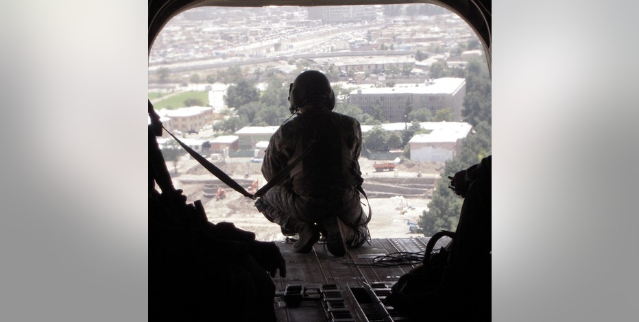 An Army soldier guards the rear of a Helicopter ferrying VIP's to Logar Provence, outside of Kabul