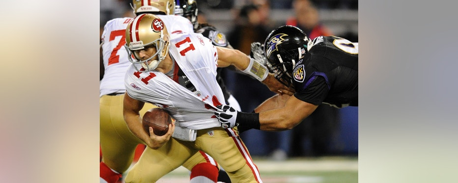 San Francisco 49ers quarterback Alex Smith (11) tries to escape the grasp of Baltimore Ravens defensive end Haloti Ngata, right, in the first half of an NFL football game, Thursday, Nov. 24, 2011, in Baltimore. (AP Photo/Nick Wass)