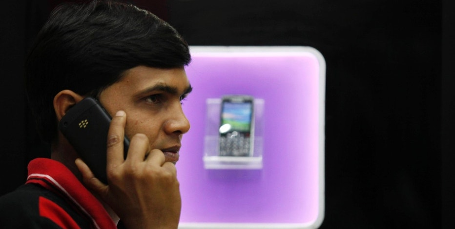 A man speaks on a BlackBerry mobile phone inside a shop in Kolkata January 31, 2011. The government will still insist that BlackBerry-maker Research In Motion give it a solution to access corporate email services, Home Minister P. Chidambaram said on Monday. REUTERS/Rupak De Chowdhuri (INDIA - Tags: BUSINESS)