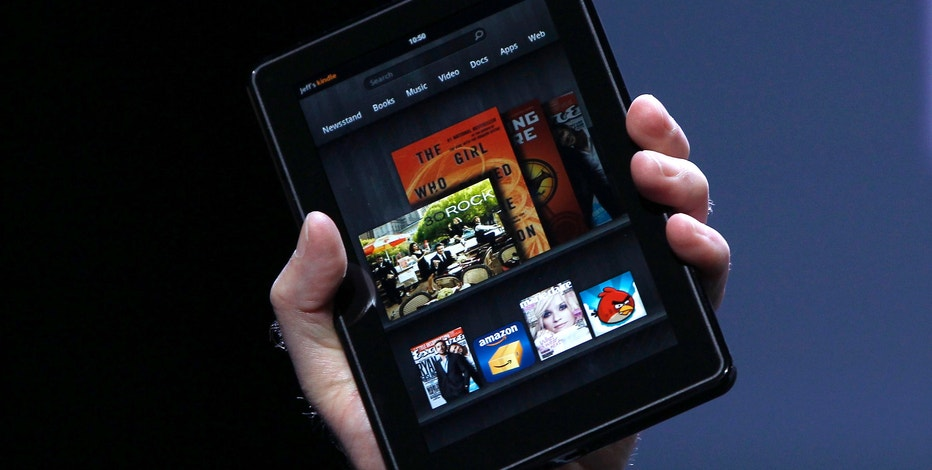 Amazon CEO Jeff Bezos holds up the new Kindle Fire at a news conference during the launch of Amazon's new tablets in New York, September 28, 2011. REUTERS/Shannon Stapleton (UNITED STATES - Tags: BUSINESS SCIENCE TECHNOLOGY)
