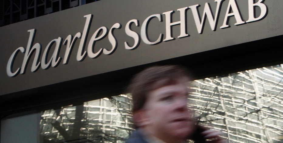 A man walks past a Charles Schwab Investment branch in Washington January 19, 2010.  REUTERS/Jim Young   (UNITED STATES - Tags: BUSINESS)