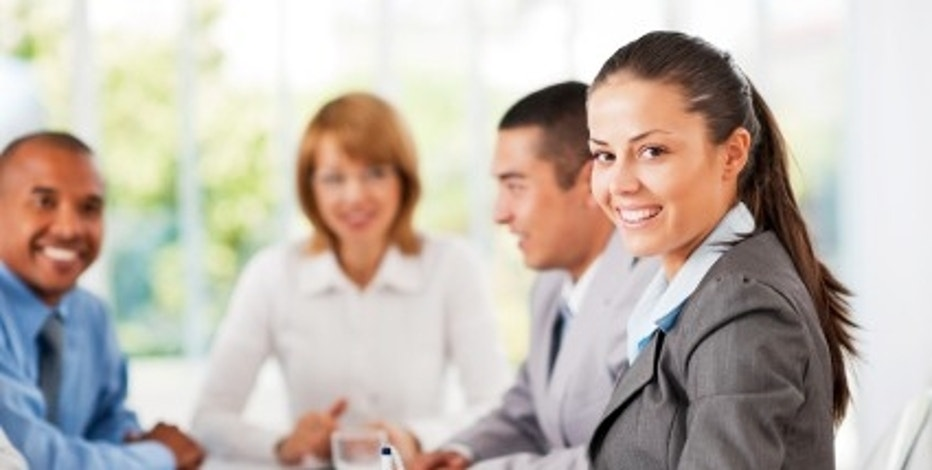 Successful group of businesspeople working in office. They are on a meeting.  The focus is on the beautiful brunette looking at the camera. 