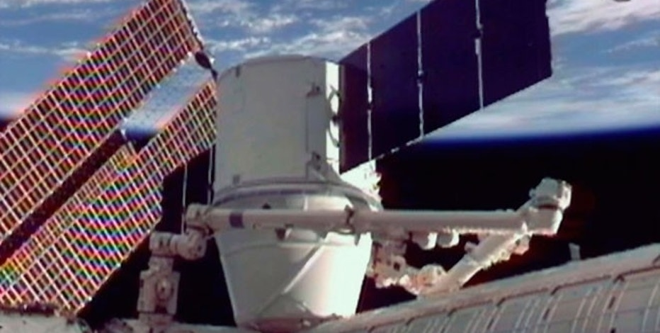 The SpaceX Dragon commercial cargo craft is seen docked to the Harmony node of the International Space Station with the Japanese Kibo Laboratory module in the foreground and the earth in the background in this image from NASA TV.