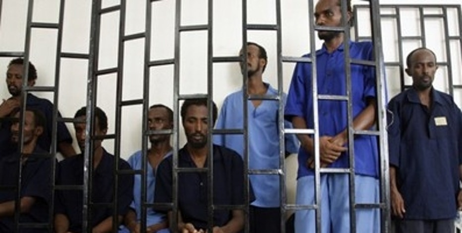 Somali suspected pirates appear behind bars of a court in Yemen's southern port city of Aden in this July 15, 2009 file photo. Pirate activity has risen steadily. The first three months of 2011 were the worst on record, the EU says, with 77 attacks and hijackings -- up from only 36 in the same period of 2010. The pirates have started using hijacked vessels -- including giant tankers the size of skyscrapers -- as mother ships, so they can operate throughout the stormy monsoon season and far further out to sea than before. The worsening situation, say experts, has made it almost inevitable that today's merchant ships will buy in their own armed protection. To match Special Report PIRATES/ REUTERS/Khaled Abdullah/Files   (YEMEN  - - Tags: CRIME LAW BUSINESS TRANSPORT)