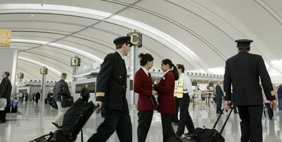 Airline pilots walk through the departures level in the new Pearson International Airport Terminal One, on its first day of operation, in Toronto April 6, 2004. The new terminal is part of a 3.6 billion dollar (US 2.74 billion) expansion plan for Canada's largest airport. REUTERS/Mike Cassese  MC/HB