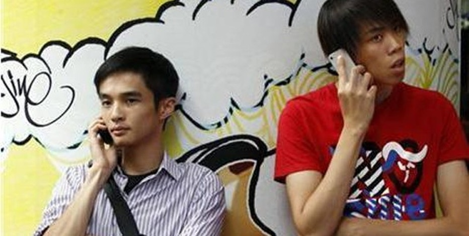Aug. 16, 2011: Two men use mobile phones as they wait outside a department store in Hong Kong.