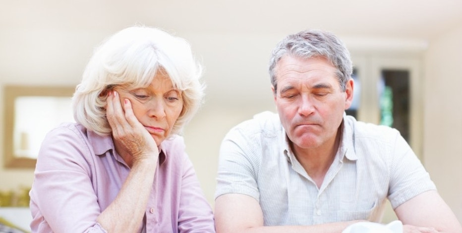 Portrait of worried senior couple planning for savings at home