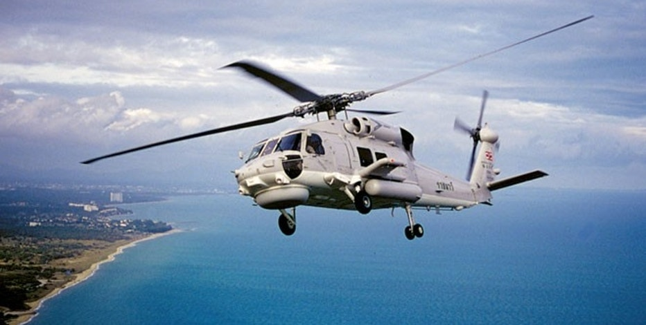An S-70B Seahawk is shown. The helicopter is manufactured by Sikorsky Aircraft, a subsidiary of United Technologies.