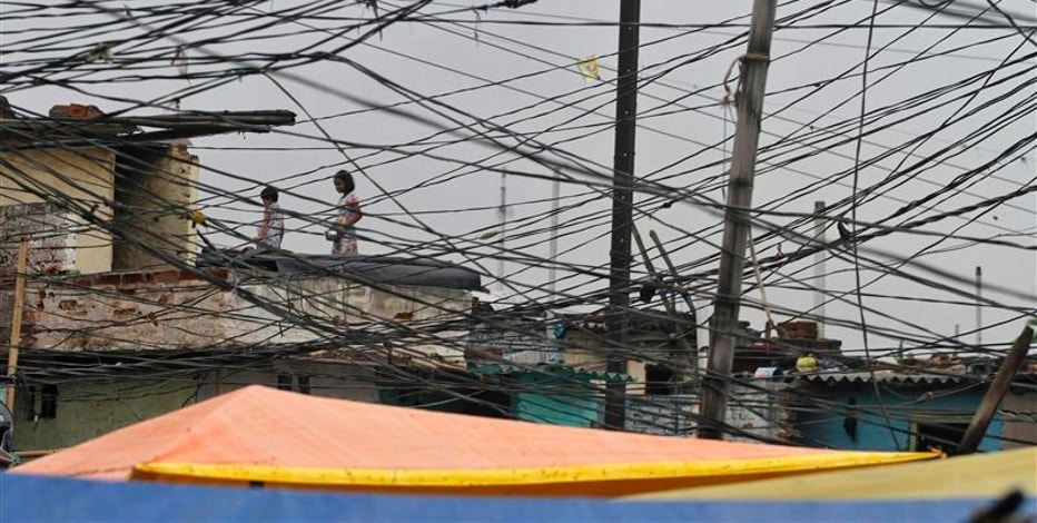 Tangled overhead electric power cables are pictured at a residential area as children stand on the roof of a house in Noida on the outskirts of New Delhi August 1, 2012.