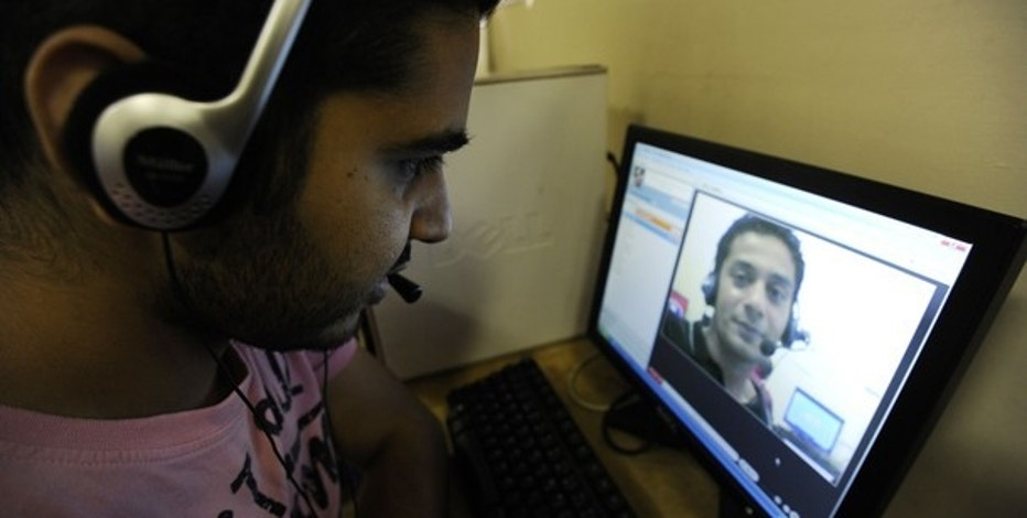 Zubair Ghumro (L) speaks to his friend Sheeraz Qazalbash using Skype software at an internet cafe in central London August 10, 2010. Internet phone services provider Skype filed to raise up to $100 million through an IPO, hoping that its wide name recognition and rapid growth will outweigh concerns that few of its customers actually pay.  REUTERS/Paul Hackett (BRITAIN - Tags: BUSINESS SOCIETY SCI TECH)