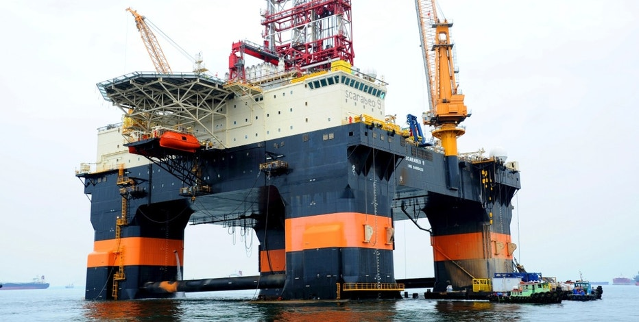 Scarabeo 9, a new Chinese-built drilling rig, is seen in Singapore in this August 26, 2011 handout photo. The Scarabeo 9, owned by Italian oil giant Eni SpA's offshore unit Saipem and contracted in Cuba by Spanish oil firm Repsol YPF, was anchored in Singapore and ready to leave on what an Eni spokesman said would be an 80-day voyage. Picture taken August 26, 2011. REUTERS/Keppel Offshore & Marine/Handout (SINGAPORE - Tags: ENERGY BUSINESS COMMODITIES) FOR EDITORIAL USE ONLY. NOT FOR SALE FOR MARKETING OR ADVERTISING CAMPAIGNS. THIS IMAGE HAS BEEN SUPPLIED BY A THIRD PARTY. IT IS DISTRIBUTED, EXACTLY AS RECEIVED BY REUTERS, AS A SERVICE TO CLIENTS
