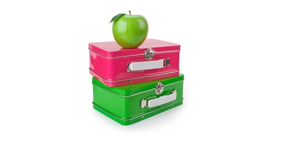 Pink and green lunchboxes with a green apple on top.  Isolated on white.