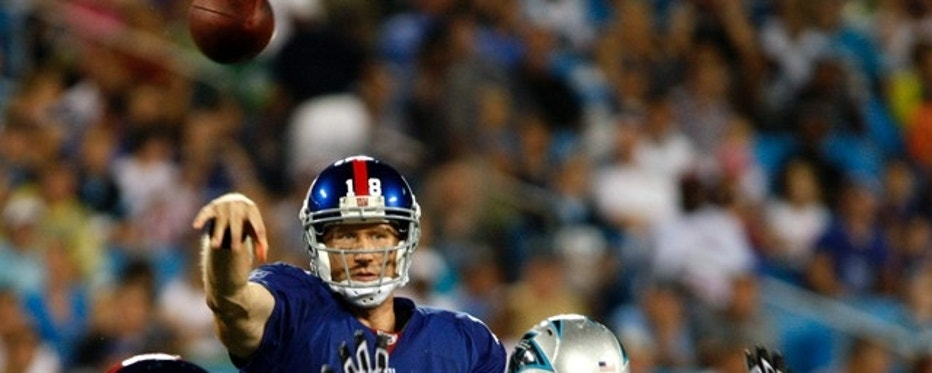 New York Giants quarterback Sage Rosenfels passes over Carolina Panthers defensive end Thomas Keiser (R) in the first half of an NFL pre-season football game in Charlotte, North Carolina August 13, 2011.   REUTERS/Nell Redmond     (UNITED STATES - Tags: SPORT FOOTBALL)