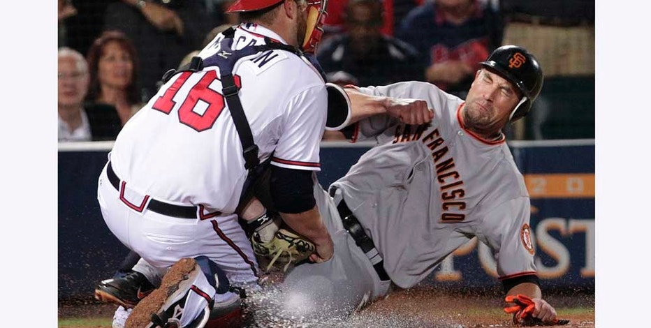 Atlanta Braves catcher Brian McCann (16) tags out San Francisco Giants' Pat Burrell at the plate during the seventh inning of Game 4 of baseball's National League Division Series on Monday, Oct. 11, 2010, in Atlanta. (AP Photo/Dave Martin)