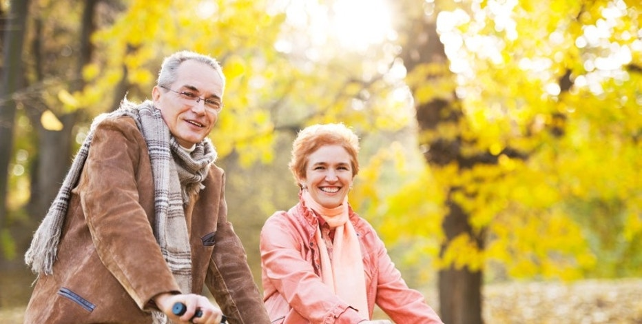 Cheerful mature adults enjoying in the autumn while riding bicycles. 