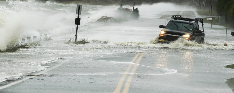 A truck drives through water pushed over a road by Hurricane Sandy in Southampton, New York, October 29, 2012. Hurricane Sandy, the monster storm bearing down on the East Coast, strengthened on Monday after hundreds of thousands moved to higher ground, public transport shut down and the stock market suffered its first weather-related closure in 27 years. REUTERS/Lucas Jackson (UNITED STATES - Tags: ENVIRONMENT DISASTER)