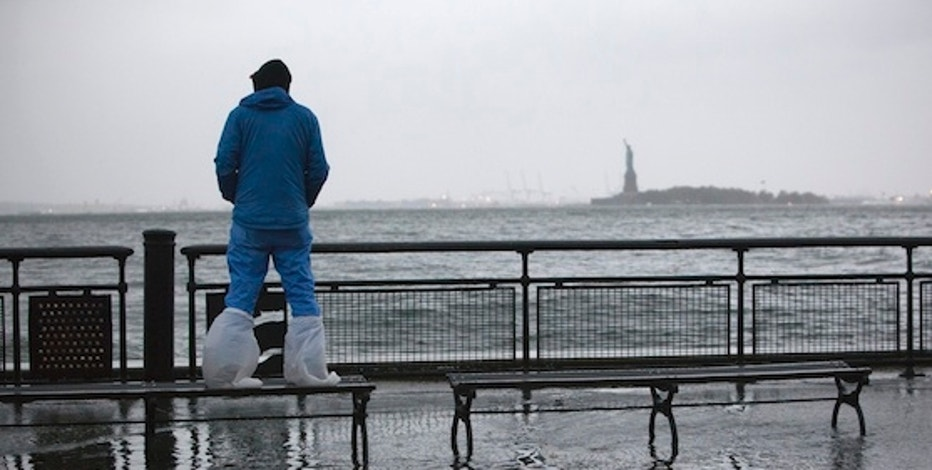 A man watches the rising tides in Battery Park as Hurricane Sandy makes its approach in New York October 29, 2012. Hurricane Sandy, the monster storm bearing down on the U.S. East Coast, strengthened on Monday after hundreds of thousands moved to higher ground, public transport shut down and the U.S. stock market suffered its first weather-related closure in 27 years. REUTERS/Andrew Kelly (UNITED STATES - Tags: ENVIRONMENT DISASTER)