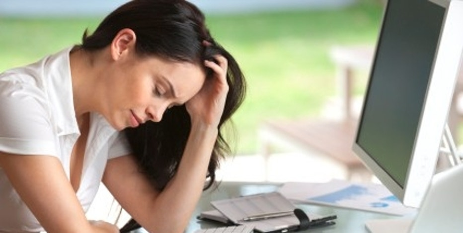 Woman looking stressed at her desk, eyes closed