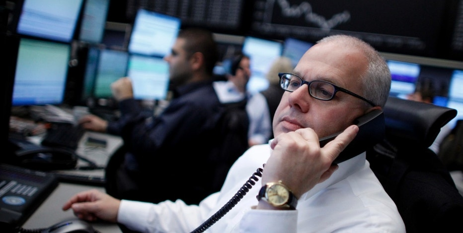 A trader makes a phone call at his desk in front of the DAX board at the Frankfurt stock exchange November 15, 2011. REUTERS/Alex Domanski (GERMANY - Tags: BUSINESS)
