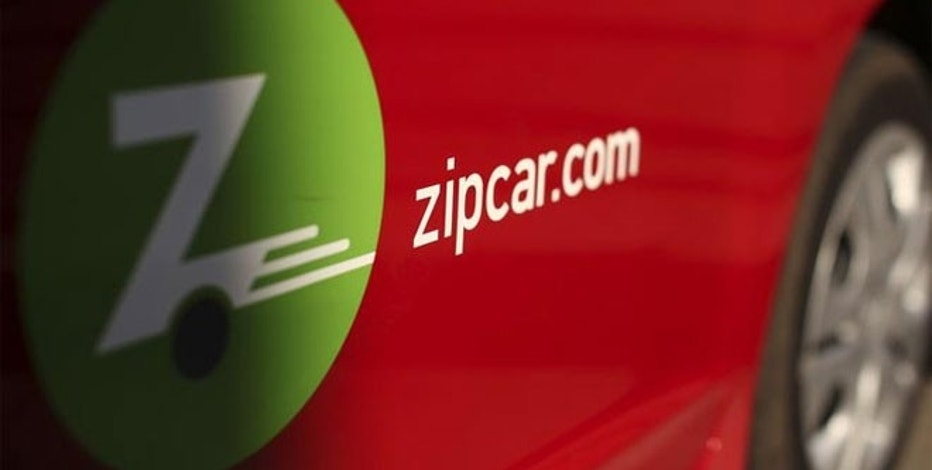 A logo is shown on the side of a Zipcar in San Francisco, California.