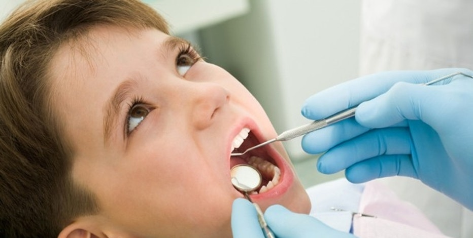 Close-up of little boy opening his mouth during dental checkup