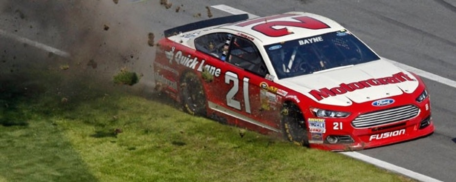 Trevor Bayne kicks up grass after running off the track in his number 21 Ford as Casey Mears trails in his number 13 Ford during the first NASCAR Sprint Cup Series Budweiser Duel at Daytona International Speedway.