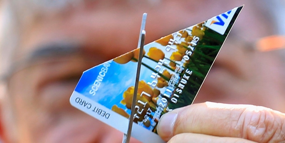 A protester cuts up his Visa card during a demonstration to get people to switch to local credit unions in San Diego, California November 2 , 2011.  REUTERS/Mike Blake   (UNITED STATES - Tags: POLITICS CIVIL UNREST)
