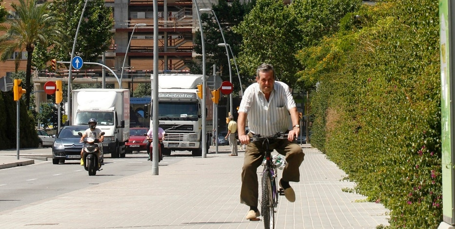 A man rides a bicycle in front of a construction site at the Diagonal Mar area of Barcelona, June 18, 2012. REUTERS/Albert Gea (SPAIN - Tags: BUSINESS CONSTRUCTION SOCIETY REAL ESTATE)