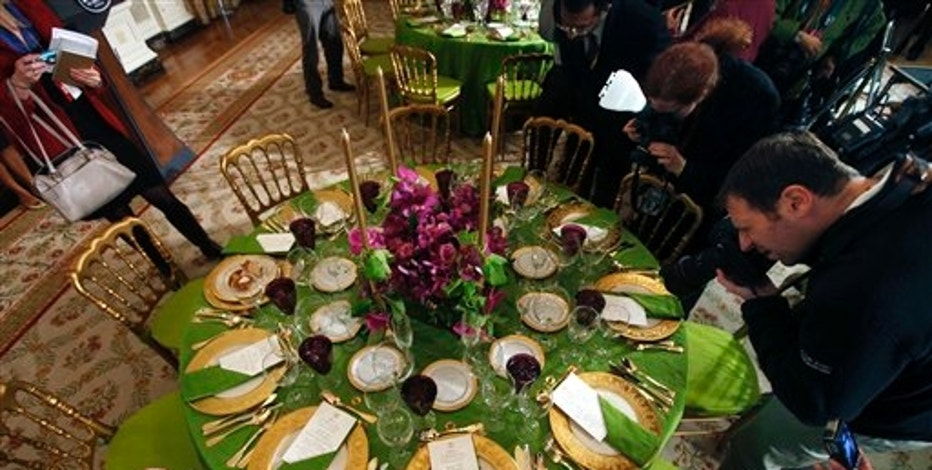 People take photos at a media event showing a sample display of a table setting prior to the State Dinner for Indian Prime Minister Manmohan Singh in the State Dining Room of the White House in Washington, Tuesday, Nov. 24, 2009. (AP Photo/Gerald Herbert)