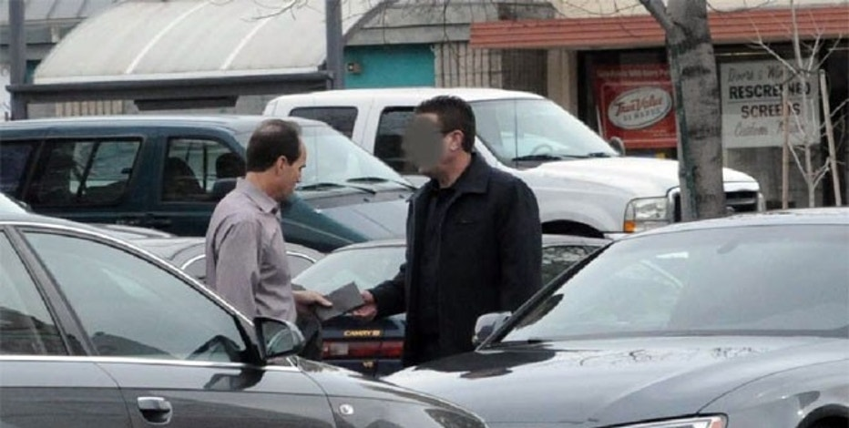 Agents with the Federal Bureau of Investigation (FBI) covertly photographed Bryan Shaw passing an enveloped filled with cash to Scott London, according to court documents.