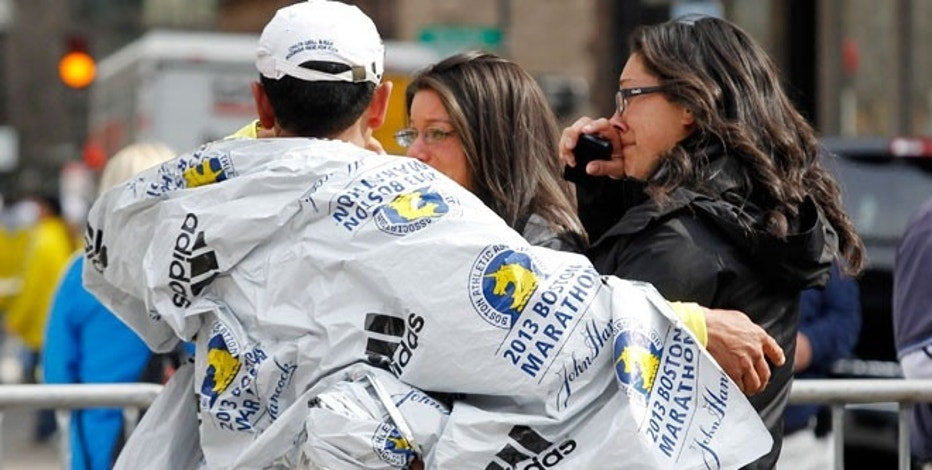 People comfort each other after explosions went off at the 117th Boston Marathon in Boston, Massachusetts April 15, 2013.