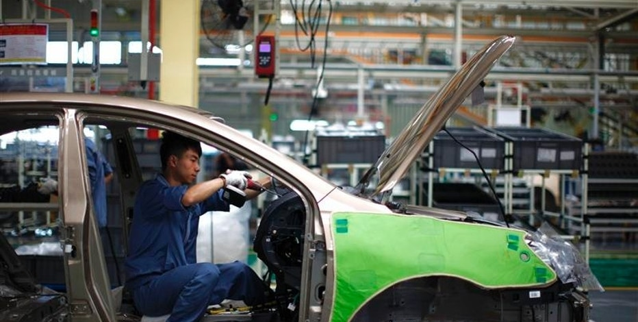 An employee works on the interior of a car along a Geely Automobile Corporation assembly line in Cixi, Zhejiang province in this June 21, 2012 file photo. REUTERS/Carlos Barria/Files