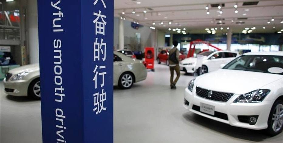 A visitor walks between Toyota Motor Corp cars displayed behind a sign in Chinese (R) and English at the company's showroom in Tokyo in this October 18, 2012 file photo. REUTERS/Toru Hanai/Files