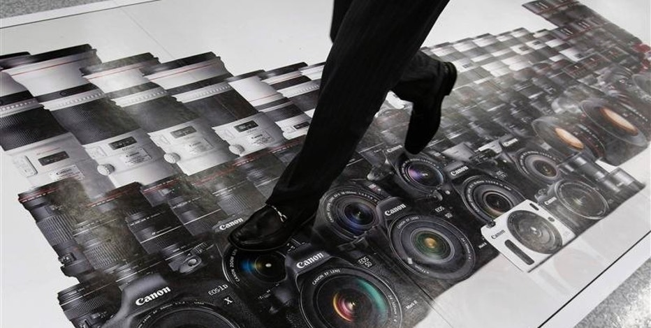A man walks on an advertisement of Canon digital cameras at an electronics retail store in Tokyo April 23, 2013. Japan's Canon Inc said first quarter operating profit fell 34 percent year-on-year, hurt by weaker demand for compact cameras as consumers switched to smartphones. Picture taken April 23, 2013. REUTERS/Toru Hanai