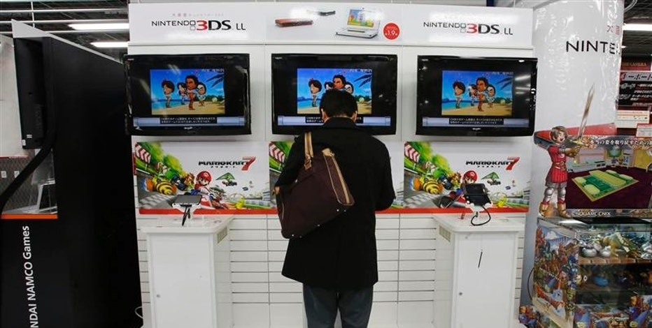A man tries out Nintendo Co Ltd's 3DS portable game console at an electronics retail store in Tokyo April 23, 2013. Nintendo Co Ltd forecast a return to profit in the year that began April 1 after a second straight annual operating loss, as a weaker yen boosts revenue and offsets worse than anticipated sales of its latest home game console, the Wii U. Picture taken April 23, 2013. REUTERS/Toru Hanai